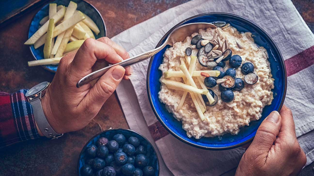 Man Eating Oatmeal With Blueberries and Apples