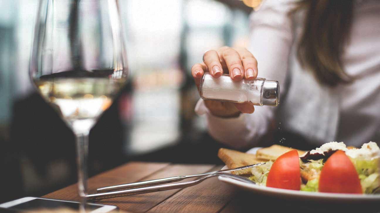 Woman Adding Salt to Food