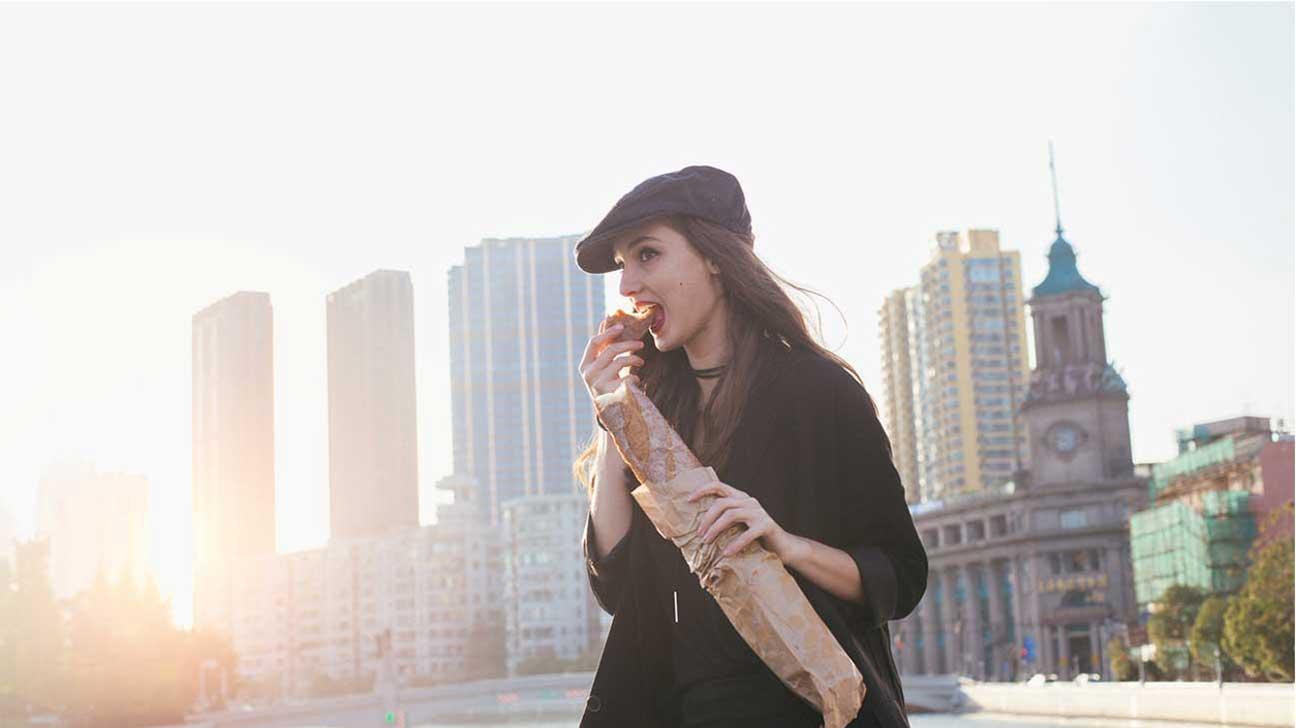 Woman Eating Baguette in City