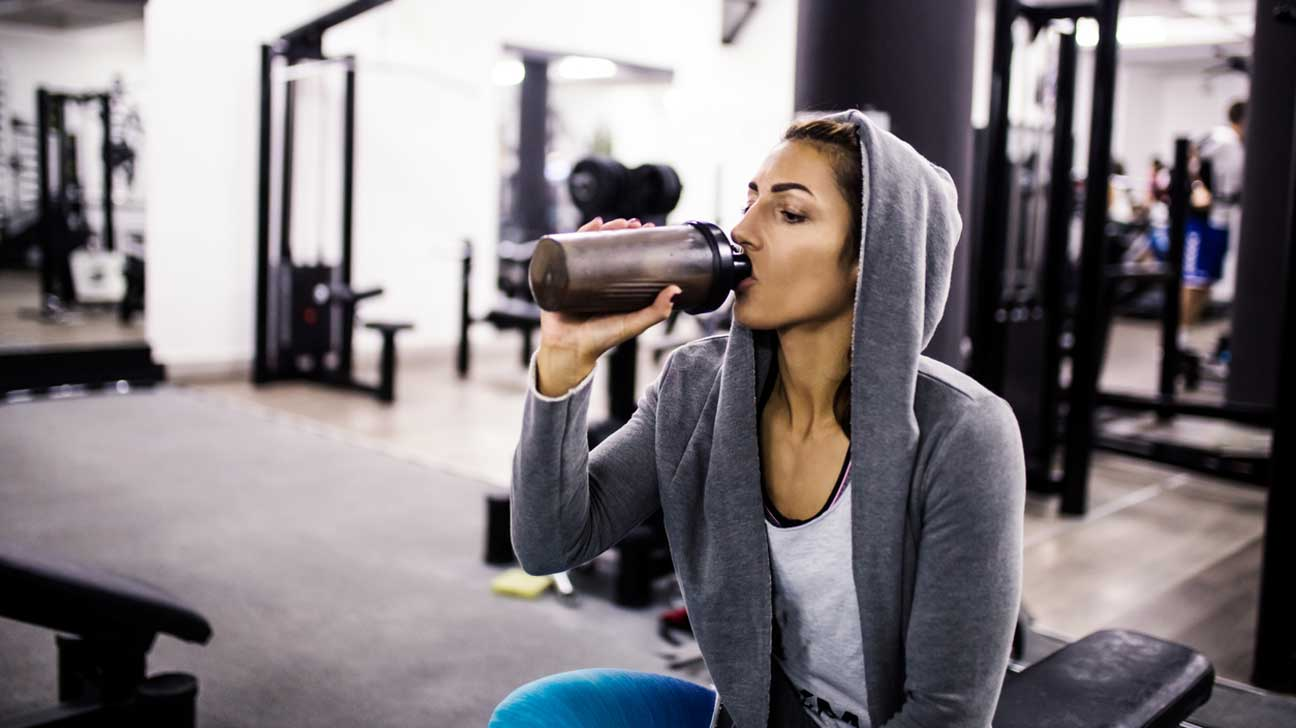 woman-in-gym-drinking-protein-shake-1296