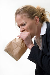 A woman breathing into a paper bag during an anxiety attack.