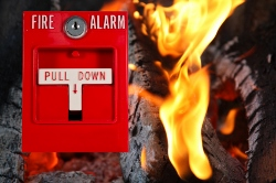 A graphic depicting a blazing fire with a fire alarm in the forefront.
