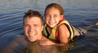 father and daughter swimming in a lake