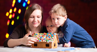 mother and sons making gingerbread house