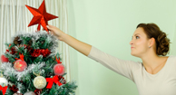 woman putting topper on christmas tree