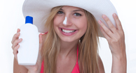 woman in sun hat holding sunscreen