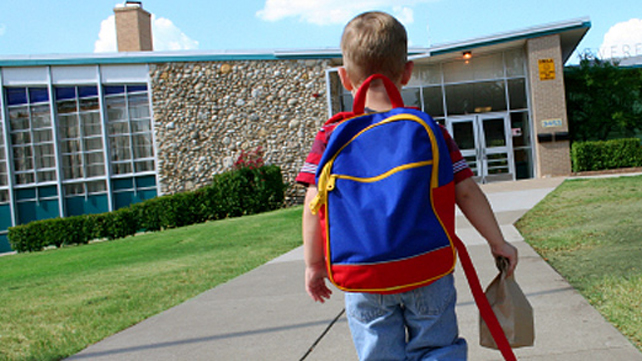 boy wearing backpack walking toward a school