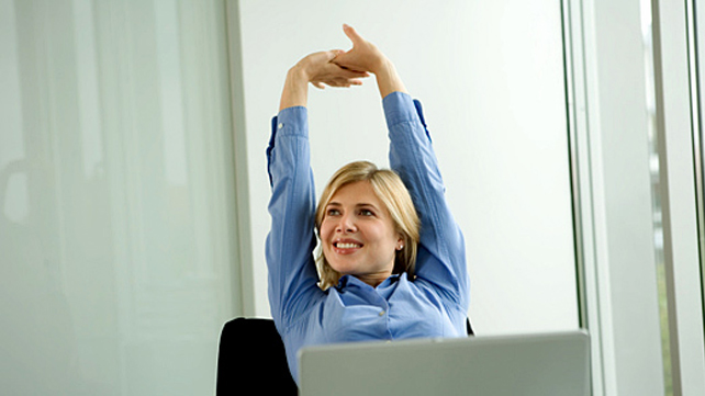 woman stretching at her work desk