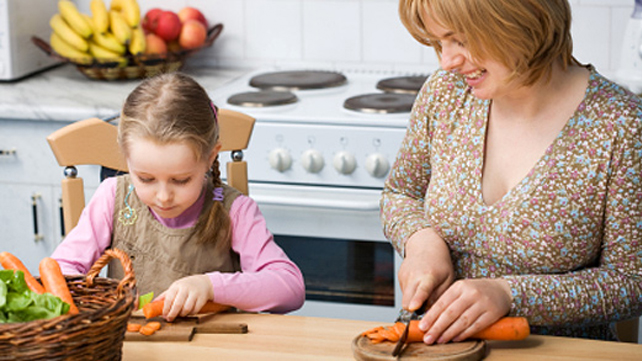 Woman preparing food with young daughter