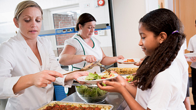 cafeteria workers serving kids food