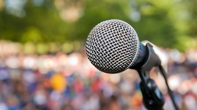 close-up of a microphone with large crowd background