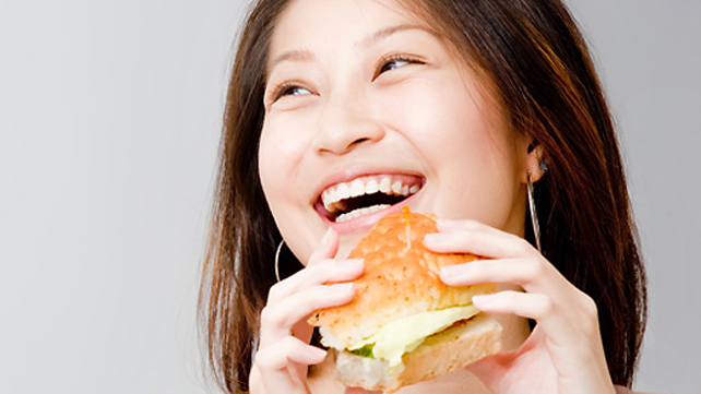 smiling woman eating a sandwich