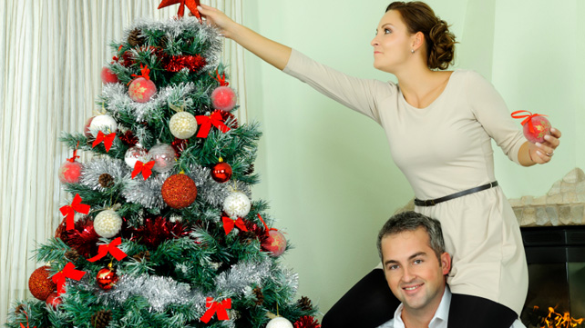 woman topping christmas tree with ornament