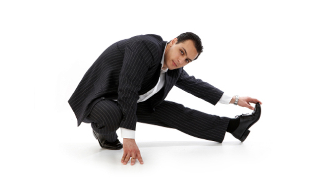 man in a suit stretching his leg