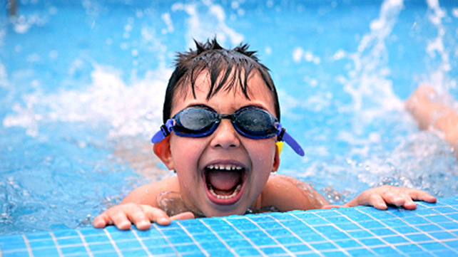 a boy with goggles enjoying a pool