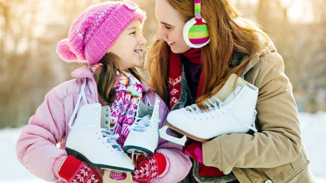 mother and daughter holding ice skates