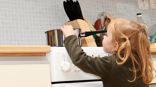 girl reaching to a pot on the stove