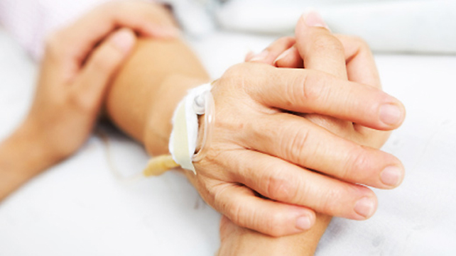 bedside supporter holding patient's hand