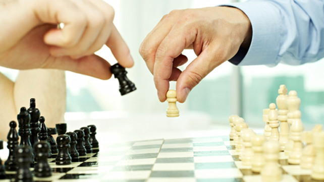 hands moving chess pieces on board