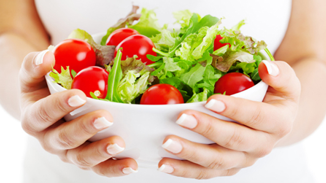 hands holding salad