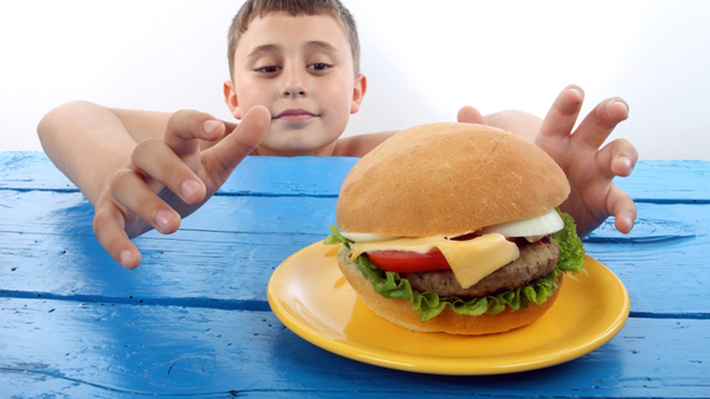 child reaching for big hamburger