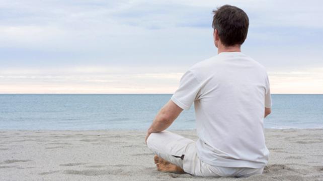 man de-stressing on beach