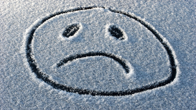 Sad face symbol drawn in snow