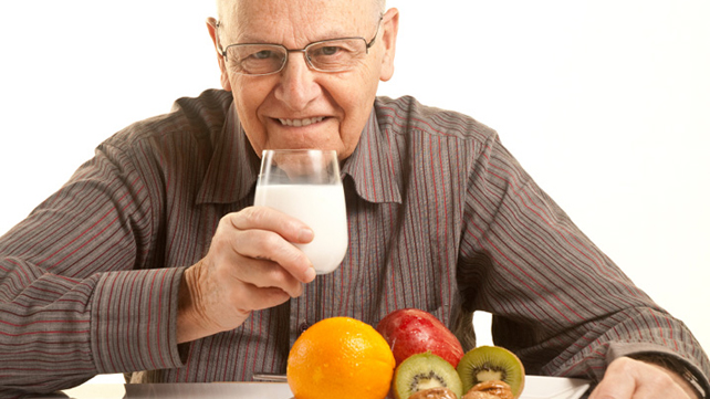 Senior man drinking milk with fruit
