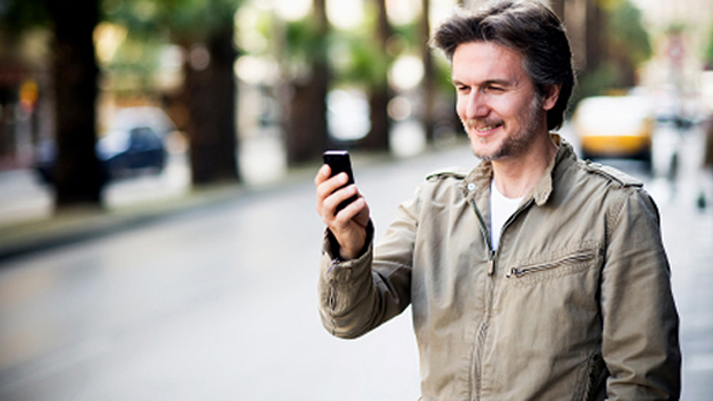 man outdoors with smartphone