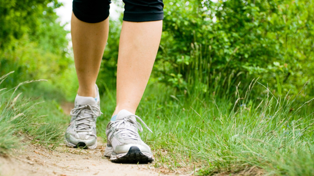 womans legs walking through grassy path