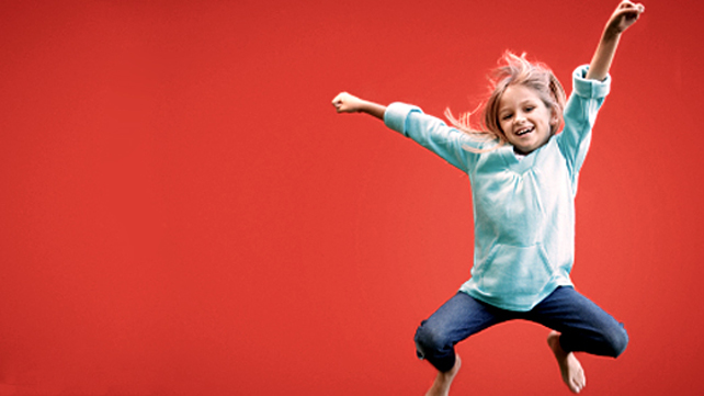 girl jumping in the air with a red background