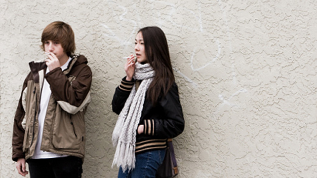 teens smoking by wall