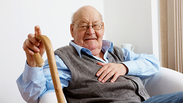 elderly man sitting with cane