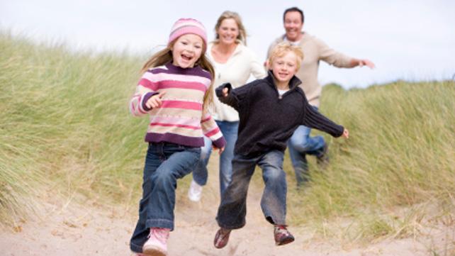 family running through sand dunes