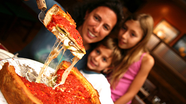 woman serving pizza to kids