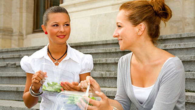 women on lunch break talking with salads