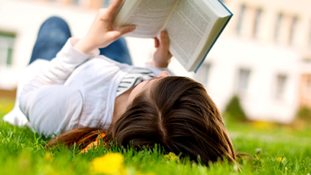woman reading book in grass