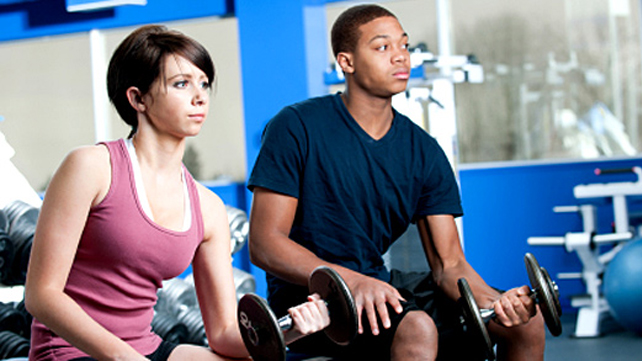 two teens in gym lifting weights
