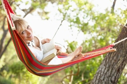 A happy woman relaxing in a hammock.
