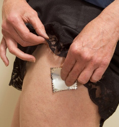 A woman applying a hormone patch.