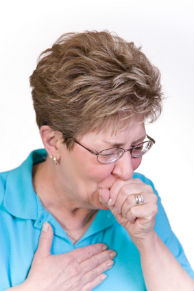 A senior woman coughing