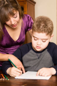 A mother helps her autistic son with his homework