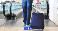 man in airport with suitcase