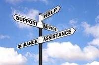 Signpost with the words Help, Support, Advice, Guidance and Assistance on the direction arrows, against a bright blue cloudy sky.