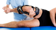 man stretching leg with knee brace