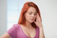 A woman holding her head in pain. Image courtesy of iStockphoto.com