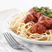 A plate of spaghetti and meatballs in red marinara sauce.