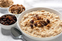 A bowl of oatmeal with raisins and walnuts.