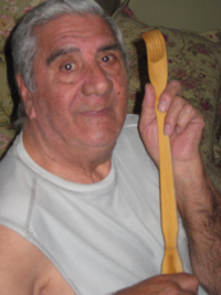 Elizabeth Santeramo's father holding a long shoehorn that helps him go about his daily tasks with COPD.