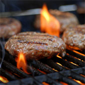 A hamburger cooking on a grill.